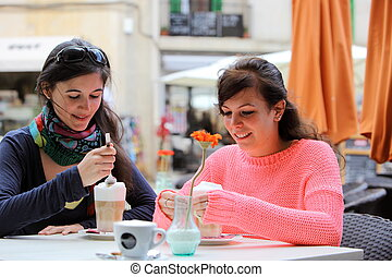 Two young women drinking cappuccino