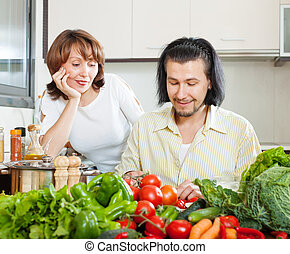 Flirting couple cooking together in  kitchen