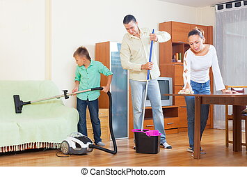 Family cleaning in living room - Happy couple with teenager...