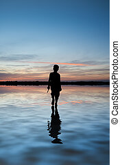 Concept image of young boy walking on water in sunset...