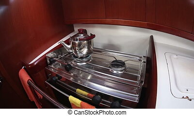 Kettle on the gas stove in yacht cook room, sailing boat