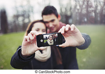 Cute young couple taking a self portrait - Cute young couple...