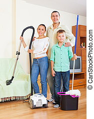 Happy family dusting in home - Happy family of three dusting...