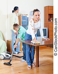 Ordinary family of three doing house cleaning with cleaning...