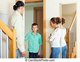 Parents meeting with scold of teenage son in doorway at home