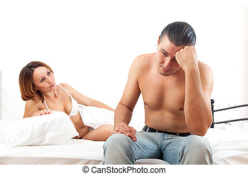 Woman consoling the depressed husband in bedroom