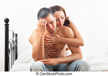 Woman consoling the depressed man in bedroom at home - Wife...