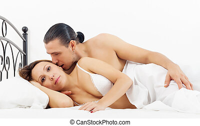 Middle-aged couple awaking in bed