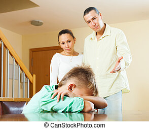 Parents berating teenager son in home. Focus on boy