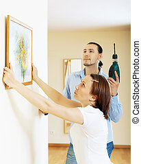 serious middle-aged couple choosing place for picture in frame on the wall at home interior