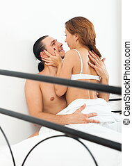 Ordinary couple in bed in bedroom