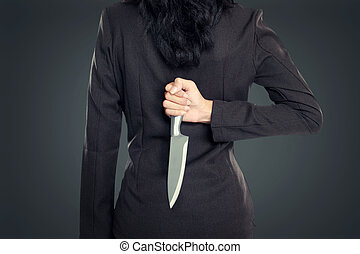 Business woman Holding Knife Behind His Back. conceptual...
