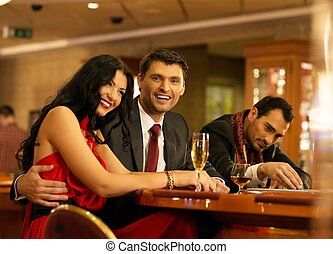 Happy young people behind gambling table with drinks