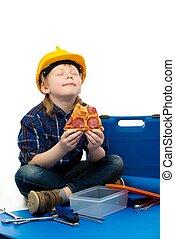 Little funny mechanic boy eating pizza among tools
