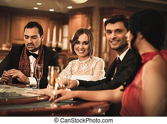 Group of happy young people behind gambling table with drinks