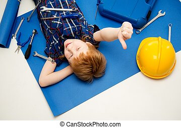 Funny little mechanic boy with wrench tools lying on a...