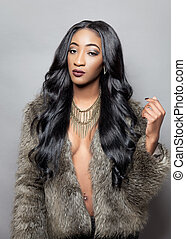 Beautiful black woman with long curly hair wearing a fur...