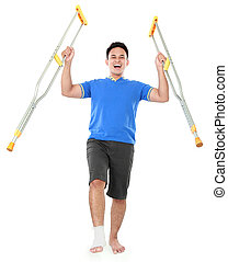 happy male with broken foot using crutch - Full length...