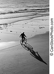 Biker on Beach - Lone Bike Rider on the Beach in Black and...