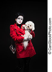 woman mime with puppy - funny woman mime holding small...