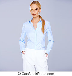 Elegant stylish blond woman in smart casuals standing in a...