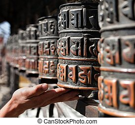 many prayer wheels and hand