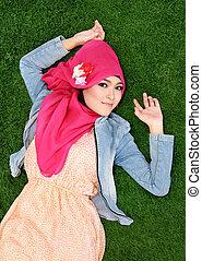 Muslim girl wearing hijab lying on grass