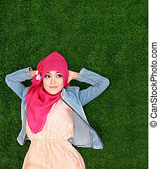 girl wearing hijab lying on grass looking up to copyspace