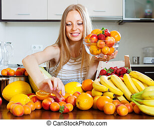 woman choosing fruits in home kitchen - Positive blonde...