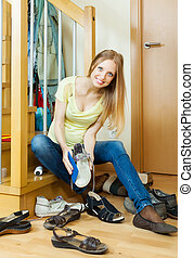Happy blonde housewife cleaning shoes