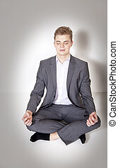 Young businessman posing, meditating. - Handsome young...