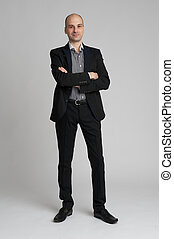 smiling confident businessman standing arms crossed