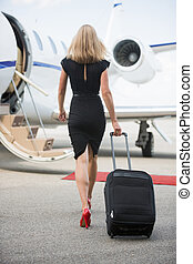 Rear View Of Woman With Luggage Walking Towards Private Jet...