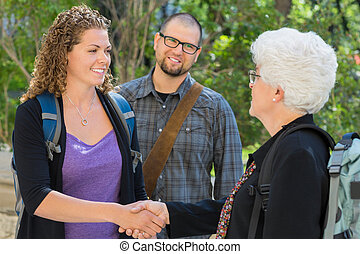 Students Shaking Hands At University Campus - Female...