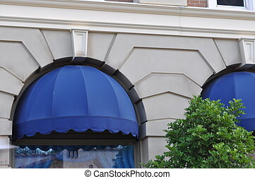 awning on building with tree in front - blue awning with...