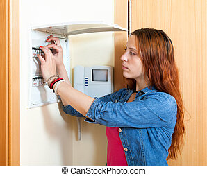 Serious woman turning off the light-switch at home