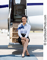 Air Hostess Sitting On Ladder Of Private Jet - Full length...