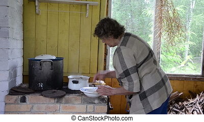 rural furnace pot woman - senior woman put into pot potatoes...