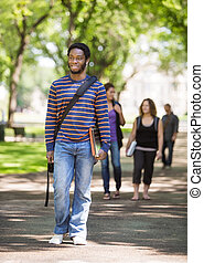Smiling Male Student Walking On Campus Road - Full length of...