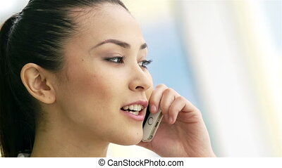 Telephone communication - Pretty woman speaking on cellular...