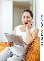 amazed mature woman looks newspaper at home