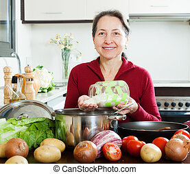 Happy mature woman cooking  with rice