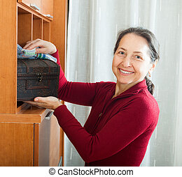 Smiling mature woman wiping the dust from wooden furniture...