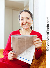 Joyful mature woman with newspaper - Joyful mature woman...