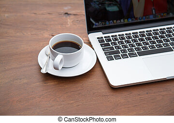 Black coffee in a white cup on a table with a computer