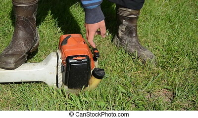 gardener start trimmer - Gardener man in gumboots hand start...