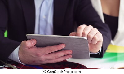 Using touchpad - Office workers using digital tablet at...