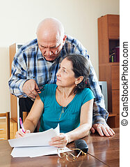 serious elderly man with wife reading documents - serious...