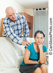 Upset mature woman with husband at home