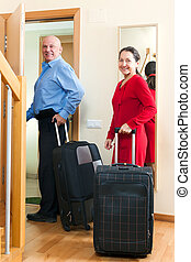 Senior tourists with luggage - positive mature couple with...